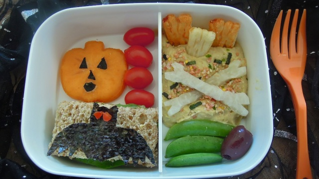 Graveyard with rice cracker tombstones set in hummus, jicama bones. Photo + Bento: Anna Mindess